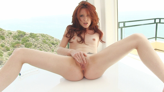 Redhead Elle Alexandra toys with her little tits, and then fucks her tight bald pussy hard and fast with a glass toy.