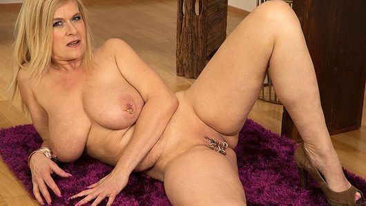 Marina Rene, a DP MILF who loves cock in her pussy and asshole, puts on a show just for you. Marina, who's from Germany, has so much going for her, it's hard to say what aspect of her is best... The fact that she's a MILF? Her big tits? The way she loves to get fucked in her pussy and asshole? The jewelry on her nipples? The bunch of big rings hanging from her pussy? The fact that she loves sex and will do anything to please a man? All of those things are true, and in this video, we get to inspect her tits, pussy and ass without any man-ass getting in the way. Yeah, we know, you love hardcore, but sometimes it's nice to see what a woman has to offer. Marina offers a lot. She's a German swinger who is married to a very giving husband. He watched while she shot these photos, and during her hardcore scenes. One of my favorite things is to have my husband's cock in my pussy and a stranger's cock in my ass while a sexy woman sucks on my tits, she said. I enjoy double penetration, and with my piercings, the sensations send me over the edge. It's amazing to have two cocks in you. Here, she has none in her, but she imagines that she does, and one of them is yours...