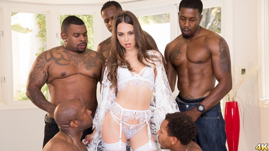 If you thought Riley Reid's first gangbang scene was intense, just wait til you see this one! Riley takes on 9 black studs in this bigger and blacker gangbang. Sweet petite Riley teases in her all white lingerie as her harem of hung studs awaits for her. Are you guys going to use me really good today? she asks as she rubs her lingerie-clad body all over them. They move inside where Riley is surrounded by more black cocks than she's ever seen, and like a good whore she starts sucking them all! She makes sure to deep throat each one as she's passed around like a joint at a Grateful Dead concert. Riley's plugged up airtight as our group of guys has their way with every one of her holes, but she's not going to be satisfied til she's covered in cum! Riley lays down in the middle of all those BBC's as they blow their loads all over her face and body and she savors every second of it. You're not going to want to miss the destruction that these 9 black bulls unleash on innocent little Riley!