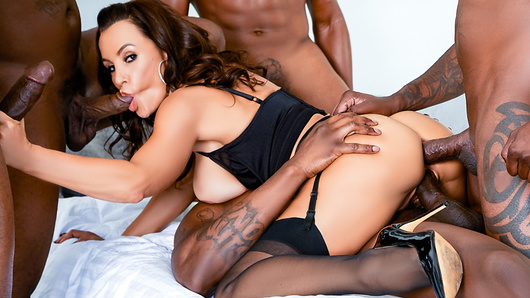Beloved MILF superstar Lisa Ann lounges on her bed in stiletto heels and classic black lingerie that can't contain her jumbo jugs. The brown-eyed beauty's twat is topped with fur. Five shirtless, muscular dudes surround her to kiss, caress and grope her trim-but-busty body. It's blowjobs all around as Lisa gasps and strokes the five big black cocks encircling her face. She keeps on sucking as one big boner packs her pussy doggie-style. The men trade off fucking Lisa's mouth and cunt, making her giddy with pleasure. At times buried under pumping pricks and other limbs, Lisa talks dirty. She sits on a cock; anal reaming leads to double penetration, and when a third dick fills her mouth, Lisa is airtight! The huge erections serially saw away at her orifices, and Lisa sucks meat ass-to-mouth. The DP date climaxes when the guys cum on her face and thick, dripping wads paste her deep cleavage.