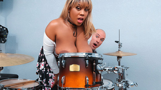 Sean Lawless wants to play his drums, but his girlfriend, Ms Yummy, wants him to play with her big boobs instead! Yummy sits on Sean's lap and grabs his drumsticks, then decides to see what noise she can make by hitting the skins with her massive jugs! Sean asks her to suck his big drumstick, and when she's got his dick good and wet with her mouth he fucks her tits. Sean needs no rehearsal to give Ms. Yummy the deep fuck she wants, and those huge breasts slap like bongos as she rides his cock! This ebony babe gets loud as Sean pounds her pussy and asks him to cum in her mouth, and he's happy to give her that massive load.