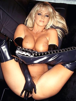 Elizabeth Hilden poses in black latex boots by a white limo