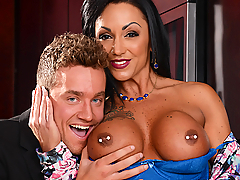 While Van's date kept him waiting while she applied her makeup, she actually gave him just enough time to get an eyeful of her hot mom, Ashton Blake. Ashton's deep cleavage, raunchy tattoos, and bronzed tan were enough to convince him that maybe he picked the wrong woman to go after. But when Ashton let him squeeze up on her massive Milfy melons, Van knew he was about to get the fuck of a lifetime. Ashton squeezed his pecker between her big fake tits, titfucking him until he couldn't handle it, and needed to get his dick wet in her pussy. Ashton rode the cock like a horny nympho, getting pounded in every position. Then Ashton gave Van a two-handed blowjob until he blew his load on her mouth and tongue.