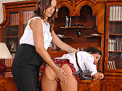 Bettina DiCapri is a bad student and has to check in with her dean, Eve Angel. Dressed in a schoolgirl outfit complete with plaid skirt and necktie, she lurks into the office looking for trouble as she chews her gum and plays with it. Eve isn't having it and decides that she needs a good old fashioned spanking. The dean bends Bettina over the desk flipping her skirt up and revealing her juicy ass. She puts a pack of cigarettes in her mouth to humiliate her and keep her from biting her tongue as she's planning on whacking it real good... She lays into her, pressing her head down onto the desk at the same time. Then she turns her around and uses her necktie first as a gag while she has her way pinching her little nipples and then to tie her hands up while Eve massages and spanks her aching pussy. You know what comes next, enjoy the views!